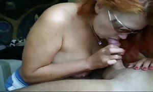 red haired mother in sunglasses is staying on her knees and deepthroating a manhood